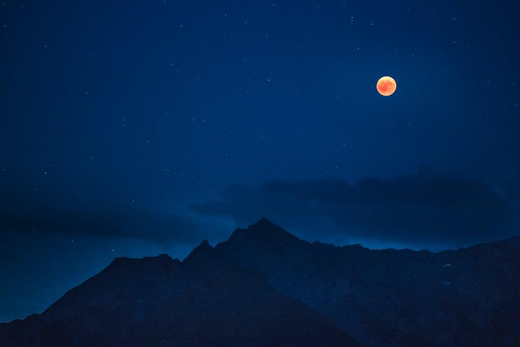 Bood moon has risen over the Signina mountains Christian Zedler Schweiz, Brigels