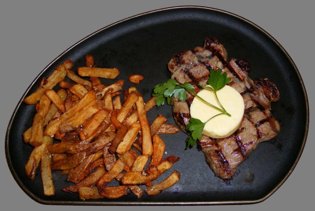 Ein Sirloin-Steak mit Knoblauchbutter und Pommes frites